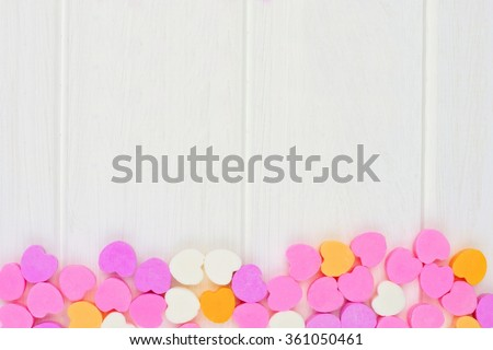Valentines Day sugar candy hearts forming a bottom border over a white wood background - stock photo