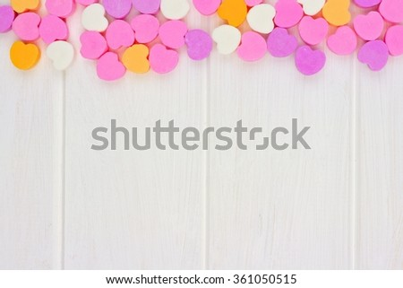 Valentines Day sugar candy hearts forming a top border over a white wood background - stock photo