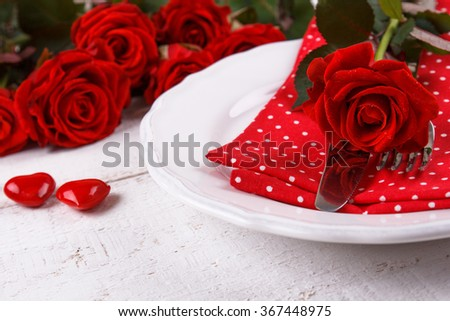 Valentines day table setting with plate, knife, fork, napkin and red roses. Valentines day background - stock photo