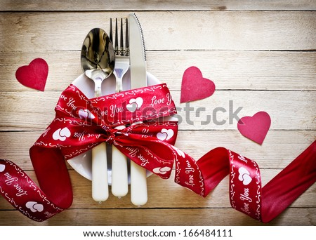Valentines day table setting with plate, knife, fork, red ribbon and hearts/ Holidays background/ Valentines day background