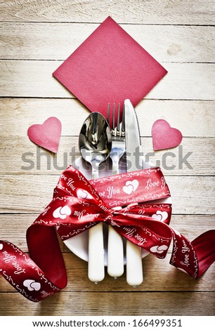 Valentines day table setting with plate, knife, fork, red ribbon and hearts/ Holidays background/ Valentines day background - stock photo