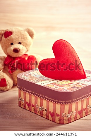 Valentines Day. Teddy Bear Loving with red hearts and gift box. Vintage. Retro Styled. Love concept on wooden background - stock photo