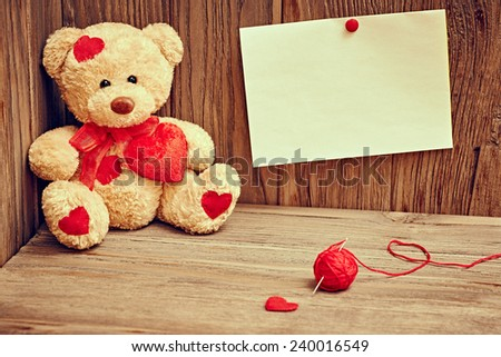 Valentines Day. Teddy Bear Loving with red hearts, note and  tangle of sewing thread. Vintage. Retro Styled on wooden background - stock photo
