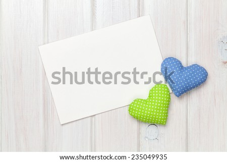 Valentines day toy hearts and greeting card over white wooden background with copy space - stock photo