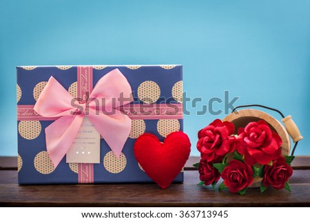 Valentines day vintage background with heart, red roses and gift box on wooden board.