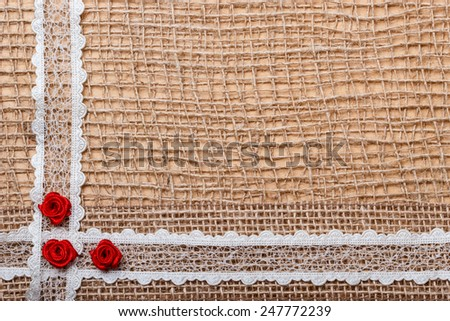 Valentines day, wedding, invitation or greeting card. Red decorative silk rose flowers, lace ribbon on rustic burlap cloth background. Border frame. - stock photo