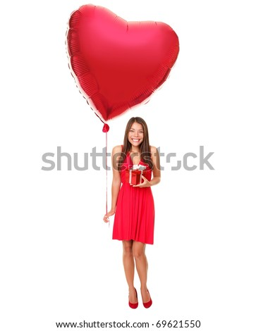 Valentines day woman holding gift and red heart balloon. Cute beautiful young woman smiling in red dress. Asian / Caucasian female model isolated on white background in full length. - stock photo
