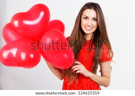 Valentines day woman holding red heart balloons - stock photo