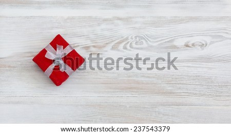 Valentines gift. Small red gift box decoratively packed into red paper and tied around with silver ribbon. Horizontal, box is on the left. - stock photo