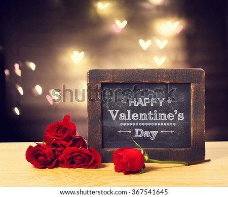 Valentines message on a small chalkboard with red roses - stock photo