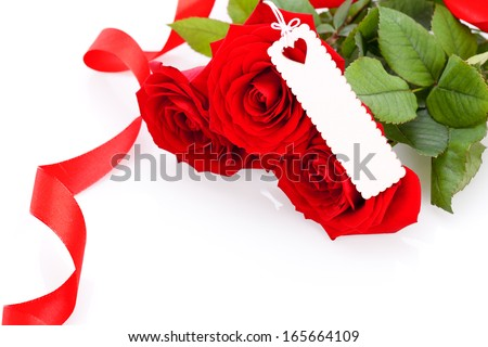 Valentines or anniversary gift of a bunch of beautiful fragrant red roses for Love with an attached decorative blank gift tag for your greetings or message - stock photo