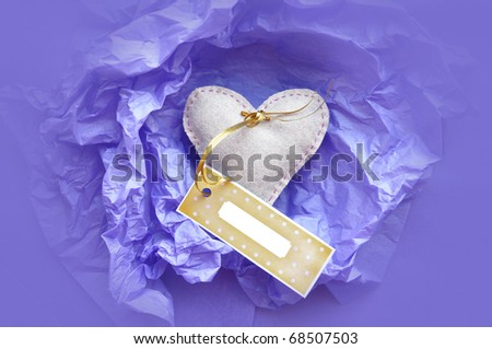 Valentines present - Heart shaped gift with a gift tag. Heart is made from felt, the tag is dotted and attached with golden ribbon. The gift is wrapped with blue tissue paper