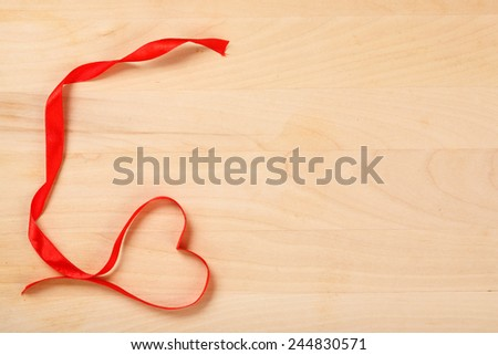 Valentines Red Ribbon  on a Wooden Background