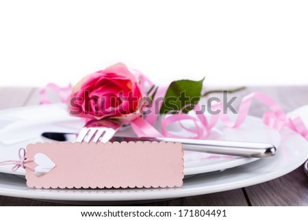Valentines table setting with an ornamental blank pink gift tag and romantic rose to celebrate the holiday with a loved one - stock photo