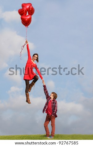 valentines teen couple flying on heart air balloons - stock photo