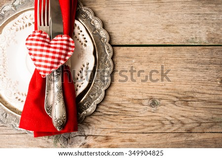 Valentines themed table setting with cloth heart utensils and silver vintage plate on a wooden background