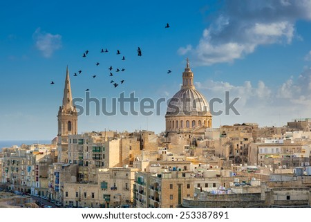 Valetta city buildings with birds flying over them, Malta - stock photo