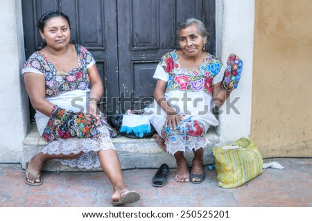VALLADOLID, MEXICO - JANUARY 20, 2015: Two women in traditional dress sit in front of old rustic building along sidewalk offering textile handicrafts for sale to tourists - stock photo