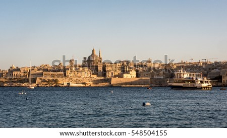 VALLETTA, MALTA - 5 FEBRUARY 2016: Valletta skyline, Malta. A view of the city skyline of the ancient capital of Malta, Valletta, with a Supreme Cruises ferry taking tourists to the old town.