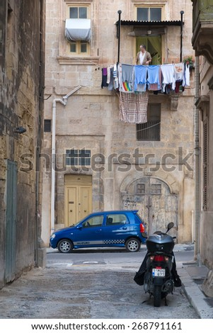 VALLETTA, MALTA - JANUARY 10, 2015: Scooter and car parked in narrow old town street with man at balcony with washing line. - stock photo