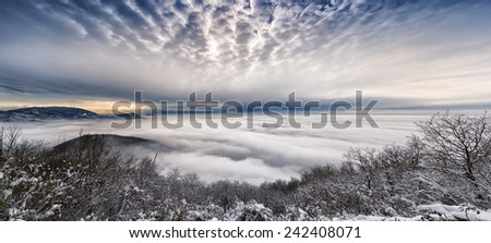 Valley covered by clouds at sunset - stock photo