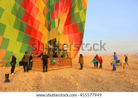 VALLEY OF THE KINGS, EGYPT -  MAY 17, 2016: People dismounting a  Hot air balloon in the morning sun  in the Valley of the Kings, Egypt, Africa - stock photo