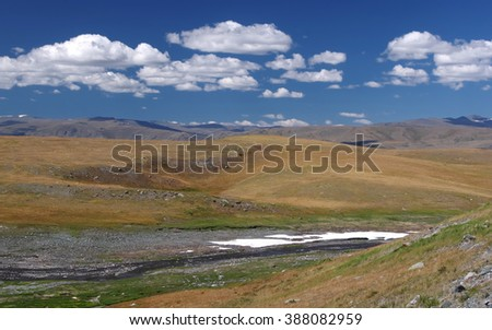 Valley of the mountain river with snow on the high plateau near Mongolia, Plateau Ukok, Altai mountains, Siberia, Russia - stock photo