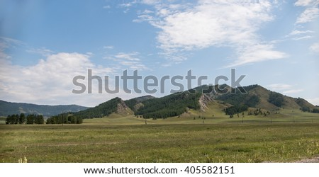 Valley. The field in front of mountains. Rays of sun through the clouds. Wooden fence. Forest.