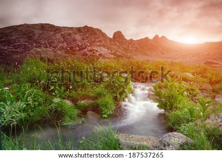 Valley with a creek in the mountains - stock photo