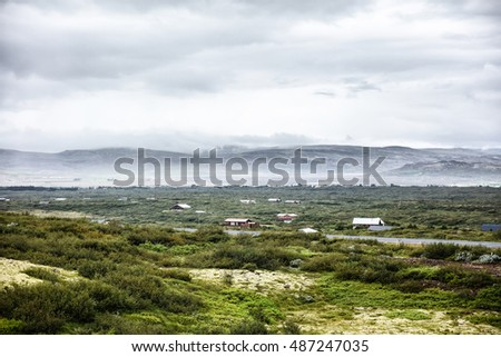 Valley with houses surrounded by hills. Icelandic landscape