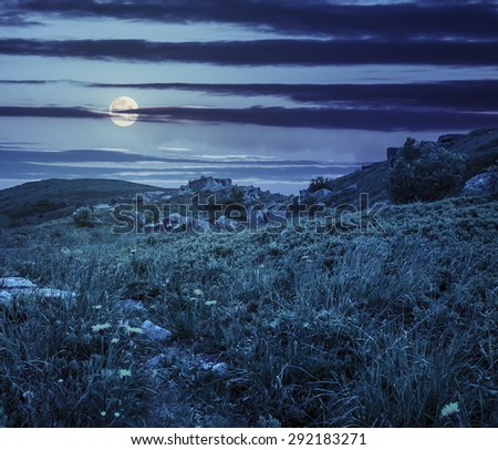 valley with stones among the grass on top of the mountain range green slope at night in full moon light - stock photo