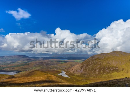 Valleys and mountains in County Kerry on a summer day with deep blue sky and white clouds in Ireland - stock photo