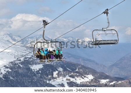 VALLOIRE, FRANCE - MARCH 24, 2015: Skiers go up the lift in Galibier-Thabor station in France. The station is located in Valmeinier and Valloire and has 150km of ski runs. - stock photo