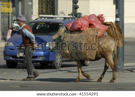 VALPARAISO, CHILE  - MAY 27:  Old world meets new as man uses a mule to transport materials through a busy city street on May 27, 2006 in Valparaiso, Chile.