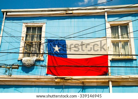 VALPARAISO - NOVEMBER 07: Chilean flag on colourful house in the Alegre district of the protected UNESCO World Heritage Site of Valparaiso on November 7, 2015 in Valparaiso, Chile - stock photo