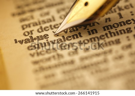 Value pen nib pointing to the words in the dictionary, shot with very shallow depth of field, - stock photo