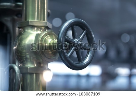 Valve wheel on brass pipe of old pumping house - stock photo