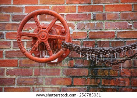 Valve wheel with chain link covered in ice from winter ice storm - stock photo