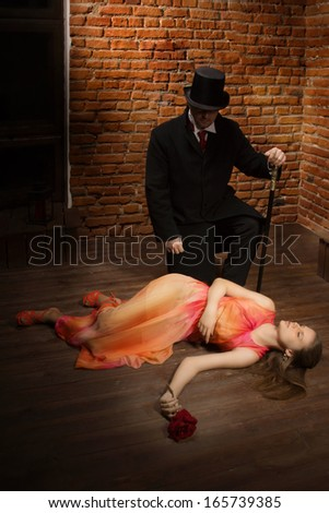 Vampire and his victim. Man in the black coat, top hat and in a red tie and beautiful girl with rose - stock photo