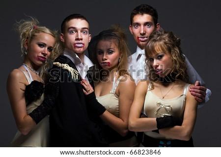 Vampire family posing on a gray background - stock photo