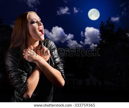 Vampire girl on night sky background - stock photo