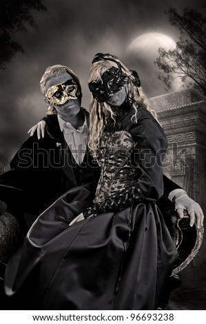 Vampire goth fashion. A young teen male and female wearing masks and dark clothing are seated in a cemetery with a full moon behind them, posing as a vampire couple. - stock photo