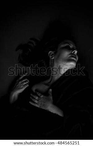 Vampire, gothic dark woman with large black cloth on gray background, Sadness