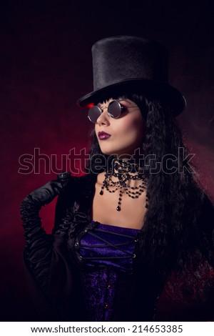 Vampire gothic girl in tophat and round eyeglasses, studio shot with smoke background  - stock photo