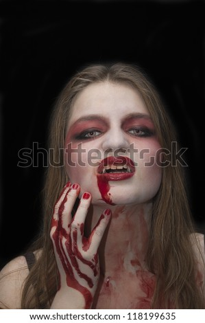 Vampire with blood in the mouth - stock photo