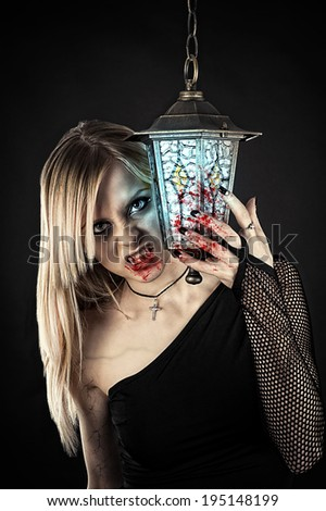 vampire with bloody fangs and hands standing near a lantern - stock photo