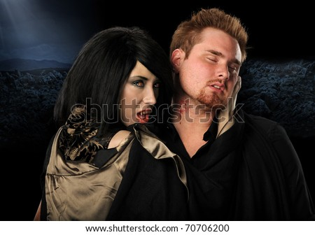 Vampire woman biting man on the neck - stock photo