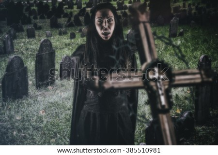 Vampire Woman Fear of the Cross. A vampire woman showing fear of a cross in a graveyard at night.