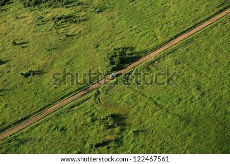 Van traveling across the Masai Mara viewed from above - stock photo