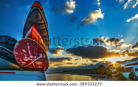 van with surfboards on the roof at sunset - stock photo
